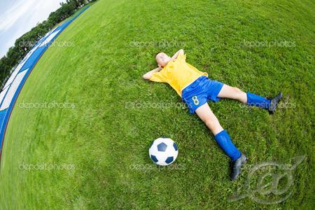 Garoto deitado no campo , sonhando em ser jogador